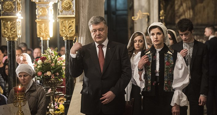 Ukrainian President Petro Poroshenko, center, and his wife Maryna Poroshenko, right, cross themselves during Orthodox Easter celebrating in the Volodymyrskiy Monastery in Kiev, Ukraine, Sunday, April 8, 2018