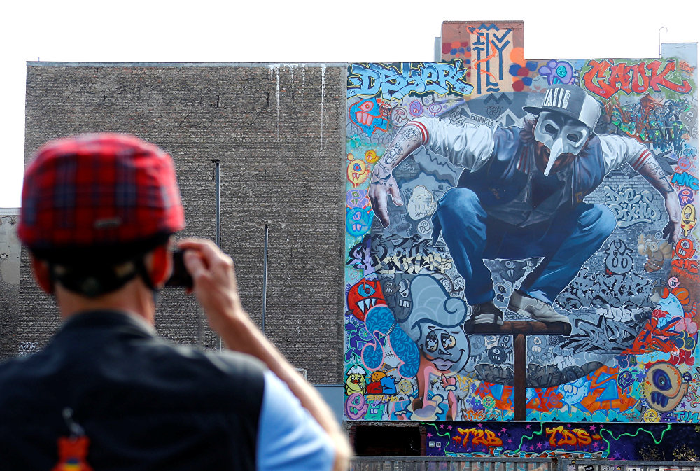 Man takes a picture of the artwork 'Kollabo Wand' as part of the first Berlin Mural Fest 2018