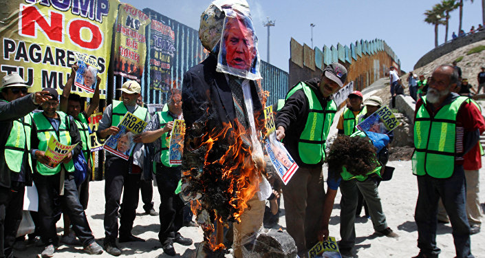 Demonstrators burn an effigy depicting U.S. President Donald Trump during a protest against the immigration policies of Trump's government near the border fence between Mexico and the U.S., in Tijuana, Mexico May 10, 2018