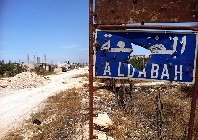 A picture taken on June 7, 2013, shows a heavily damaged sign signaling the entrance of Dabaa, north of Qusayr, in Syria's central Homs province.