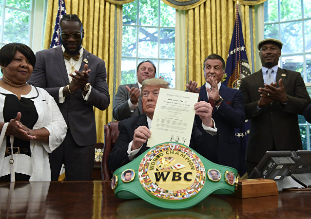 President Trump holds up the pardon as Deontay Wilder (left) and Lennox Lewis (right) applaud