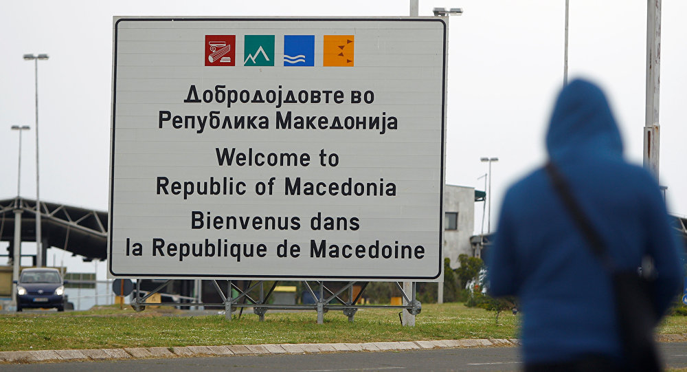A person walks near a sign that reads welcome to Macedonia at the Macedonia-Greece border April 16, 2018