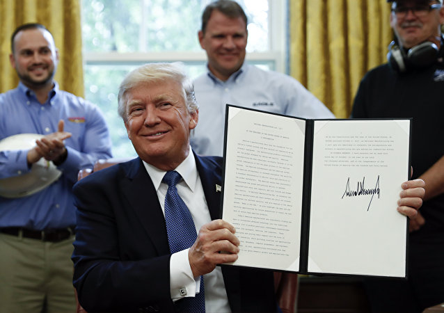 President Donald Trump holds up a National Manufacturing Day Proclamation after signing it in the Oval Office of the White House in Washington, Friday, Oct. 6, 2017