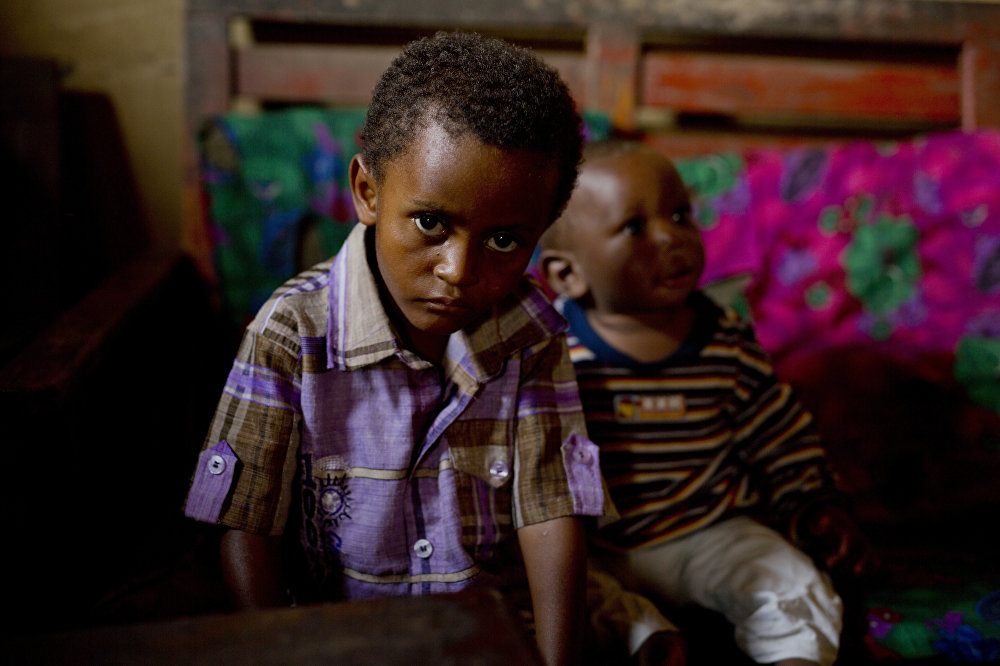 In this photo taken Aug. 10, 2016, 8-year-old Michael sits at his mother's house in the Congo Ituri province capital Bunia. Michael has never met his father, and only knows that he was a foreigner from one of the peacekeeping missions in the country.