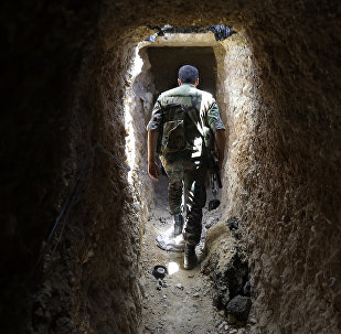A Syrian army soldier makes his way in a tunnel reportedly previously used by rebel fighters in Jobar, a mostly rebel-held area on the eastern outskirts of Damascus on June 2, 2014
