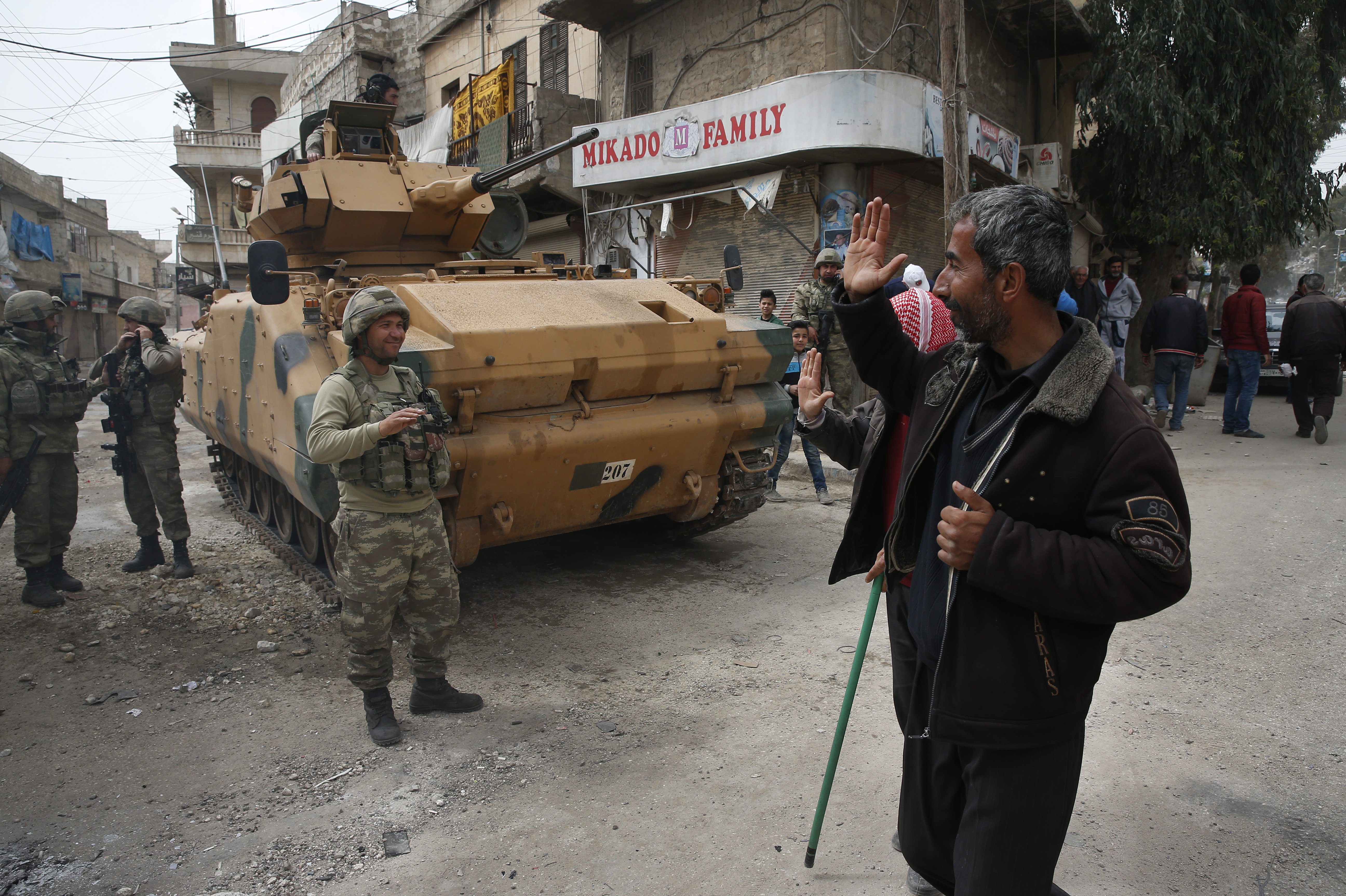 A Syrian man waves to Turkish soldiers securing the streets of the northwestern city of Afrin, Syria, during a Turkish government-organised media tour into northern Syria, Saturday, March 24, 2018