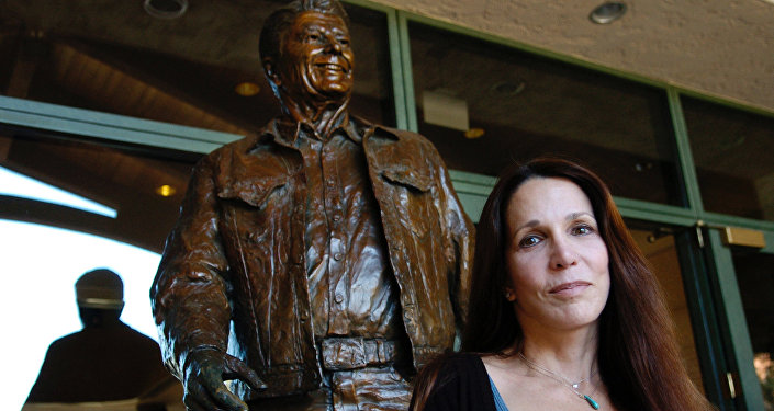 Patti Davis, daughter of late U.S. president Ronald Reagan, poses near artist Glenna Goodacre's sculpture of her father at the Ronald Reagan Presidential Library in Simi Valley, Calif., Nov. 20, 2004