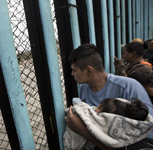 In this April 29, 2018 file photo, a member of the Central American migrant caravan, holding a child, looks through the border wall toward a group of people gathered on the U.S. side, as he stands on the beach where the border wall ends in the ocean, in Tijuana, Mexico, Sunday, April 29, 2018