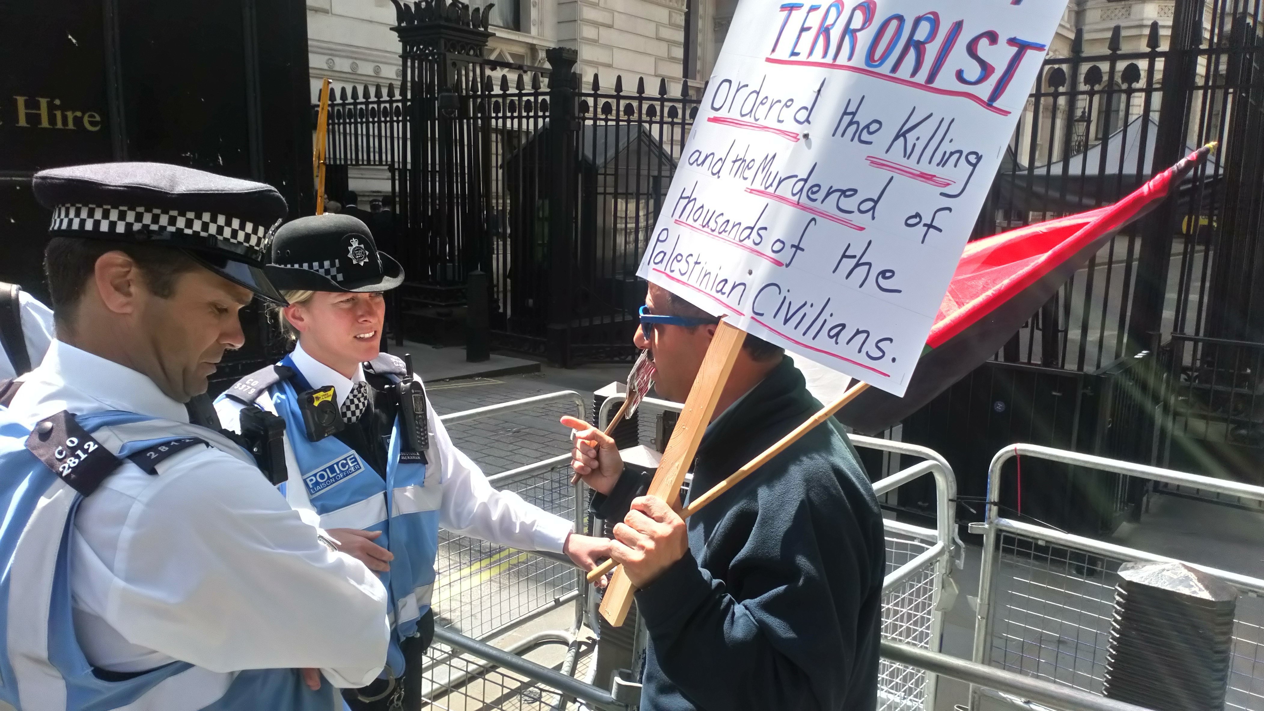 A protester demonstrates with police outside Downing Street