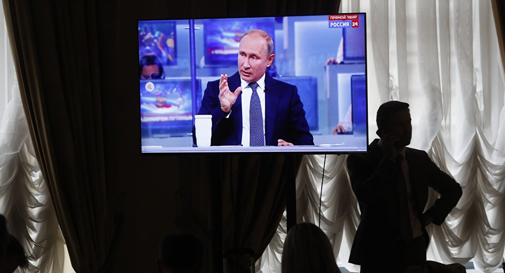 A journalist speaks on the phone while Russian President Vladimir Putin gestures answering a question during his annual call-in show in Moscow, Russia, Thursday, June 7, 2018