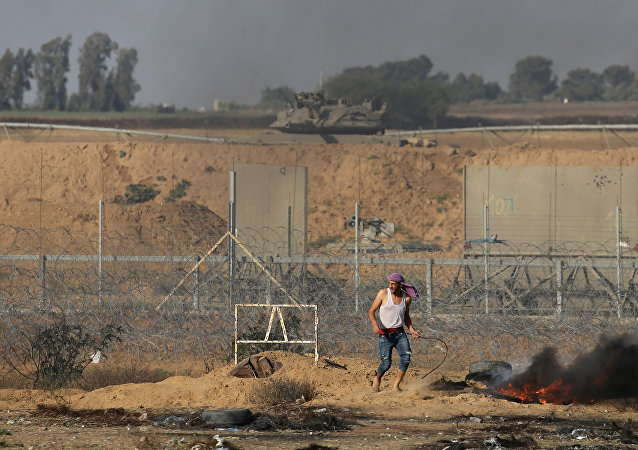 A Palestinian demonstrator stands next to the Israeli fence during a protest marking Naksa, at the Israel-Gaza border in the southern Gaza Strip June 5, 2018