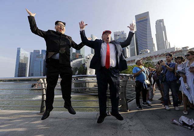 Kim Jong-un and Donald Trump impersonators, Howard X, left, and Dennis Alan, second left, pose for photographs during their visit to the Merlion Park, a popular tourist destination in Singapore, on Friday, June 8, 2018