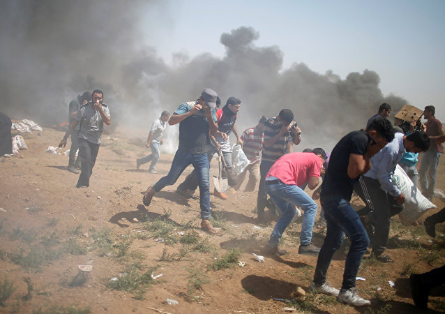 Palestinian demonstrators run for cover from tear gas fired by Israeli troops during a protest at the Israel-Gaza border