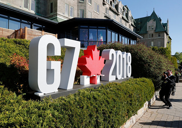 A photojournalist takes pictures of the G7 sign before the start of the G7 Summit in La Malbaie, Quebec, Canada, June 8, 2018. REUTERS/Yves Herman