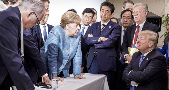 German Chancellor Angela Merkel, center, details policy to US President Donald Trump, seated at right, during the G7 Leaders Summit in La Malbaie, Quebec, Canada, on Saturday, June 9, 2018