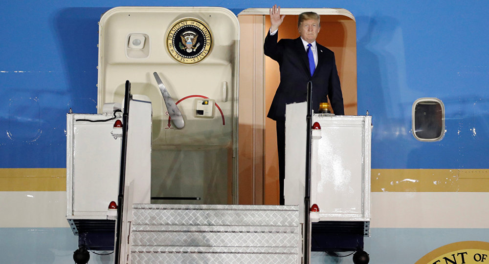 US President Donald Trump waves upon his arrival at Paya Lebar Air Base in Singapore, before his summit with North Korean leader Kim Jong Un, June 10, 2018.