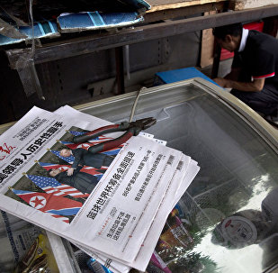A worker makes repairs at a newspaper stand with front page photos of the meeting in Singapore between U.S. President Donald Trump and North Korean leader Kim Jong Un in Beijing, China, Tuesday, June 12, 2018