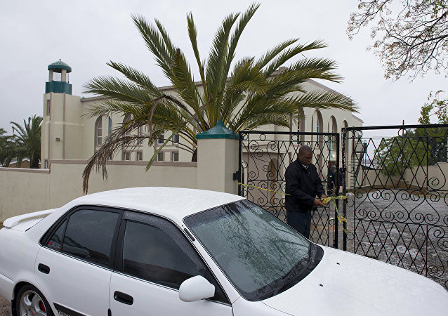 An investigator attends to the gates of a mosque in Malmesbury, near Cape Town, South Africa Thursday June 14 2018