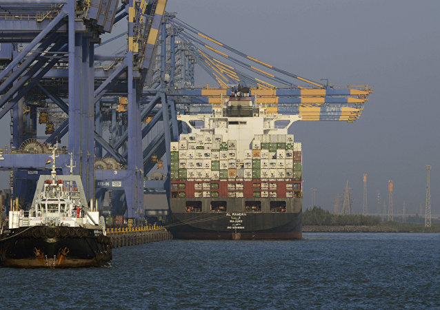 This photo taken on December 21, 2016 shows a container ship (R) docked at India's Adani Port Special Economic Zone (APSEZ) in Mundra