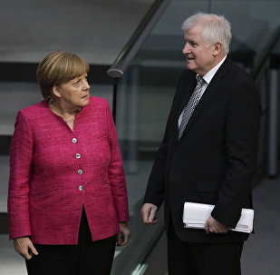 German Chancellor Angela Merkel, left, talks with German Interior Minister Horst Seehofer, right, during the first day of the budget 2018 debate at the parliament Bundestag at the Reichstag building in Berlin, Tuesday, May 15, 2018