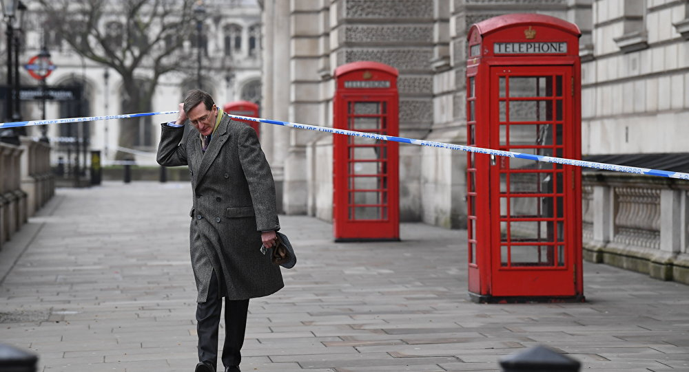 British politician Dominic Grieve lifts the police cordon as he walks along Whitehall in Westminster, central London (File)
