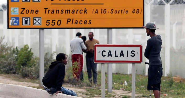 Migrants stand near a city sign along a road near the makeshift camp called The New Jungle in Calais