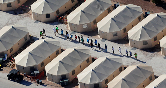 Immigrant children now housed in a tent encampment under the new zero tolerance policy by the Trump administration are shown walking in single file at the facility near the Mexican border in Tornillo, Texas, U.S. June 19, 2018