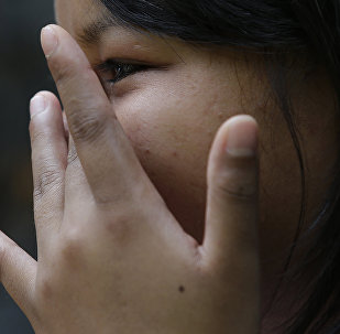 A child who was sexually exploited in the Philippines by a cybersex ring wipes away a tear