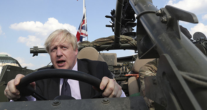 Britain's Foreign Secretary Boris Johnson talks to a British armed forces serviceman based in Orzysz, in northeastern Poland, during a ceremony at the Tomb of the Unknown Soldier and following talks on security with his Polish counterpart Jacek Czaputowicz in Warsaw, Poland, Thursday, June 21, 2018