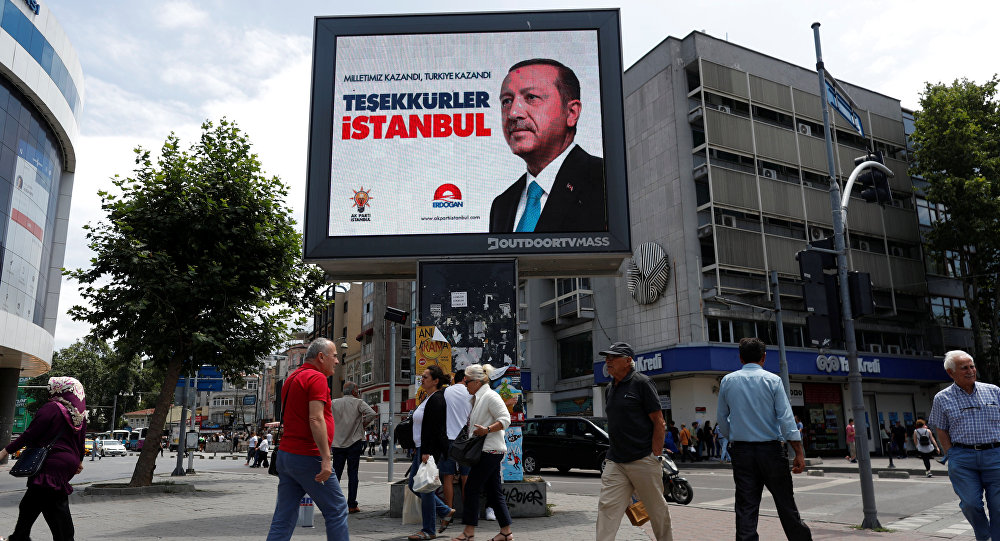 People walk past a poster for Turkey's President Tayyip Erdogan in Istanbul, Turkey, June 25, 2018. The poster reads: Our people won, Turkey won, Thank you istanbul