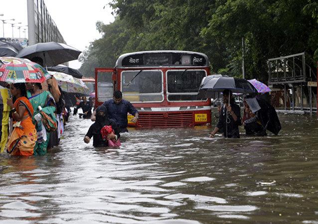 People walk through a waterlogged street following heavy rains in Mumbai, India