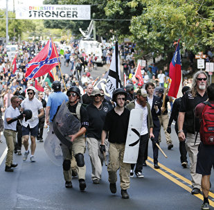 White nationalist demonstrators walk through town after their rally was declared illegal near Lee Park in Charlottesville, Va.