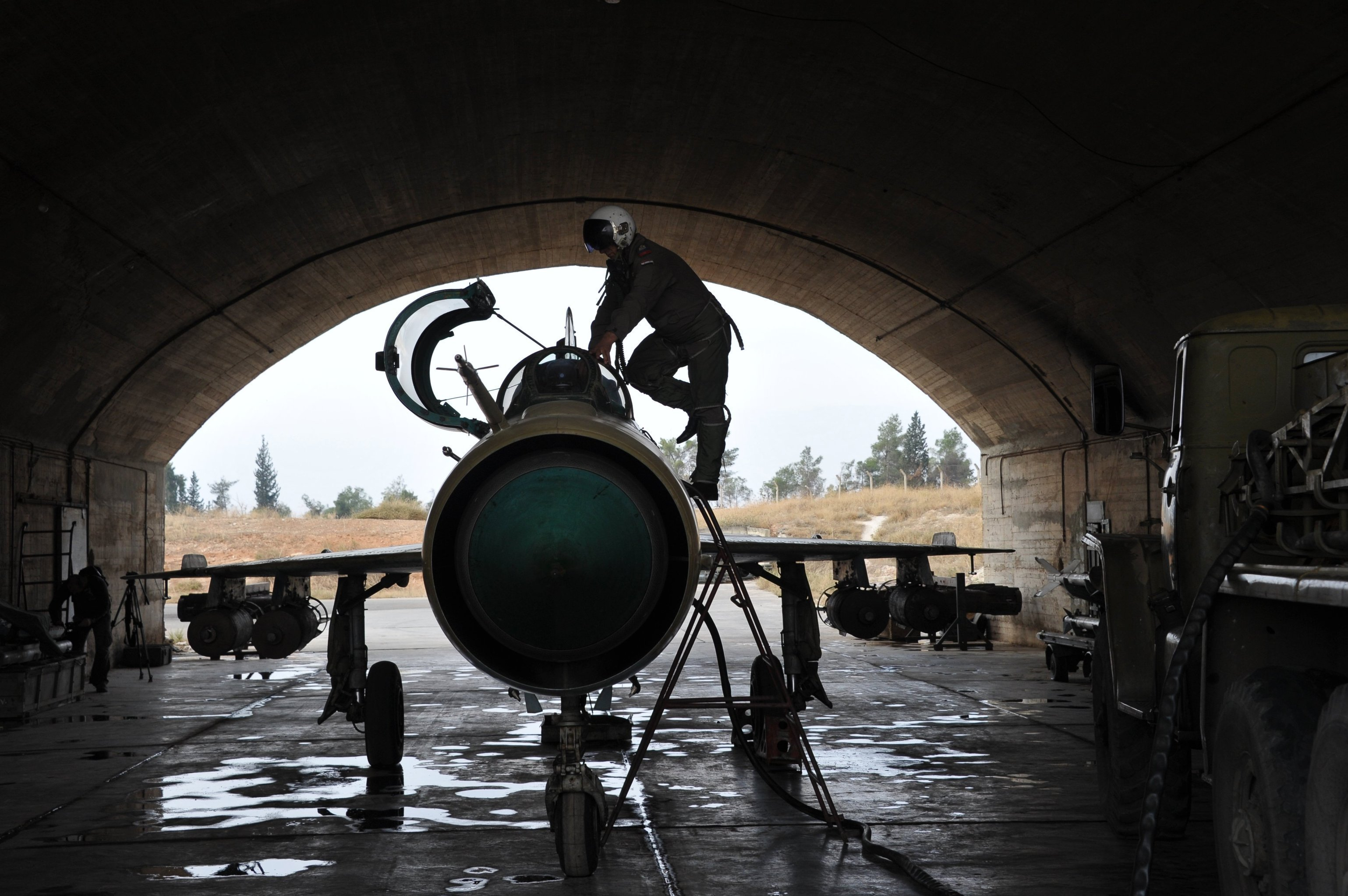 A Syrian pilot checks a MiG-21 aircraft of the Syrian Air Force before a mission at the Hama airbase near the city of Hama, Syria's Hama Province. (File)