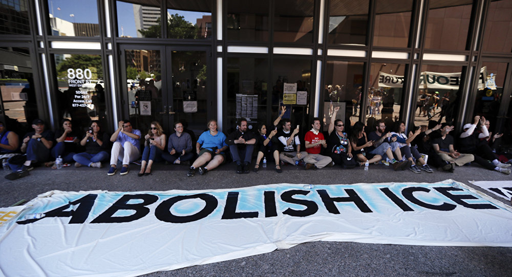 Protesters block the entrance to a downtown federal building housing Immigration and Customs Enforcement (ICE) offices Monday, July 2, 2018, in San Diego.