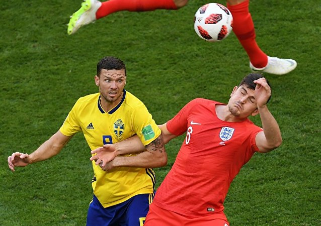 Sweden's Marcus Berg, left, and England's Harry Maguire struggle for a ball during the World Cup quarterfinal soccer match between Sweden and England, at the Samara Arena, in Samara, Russia, July 7, 2018