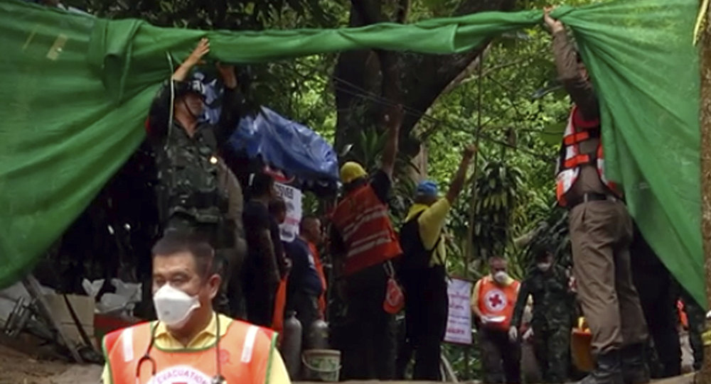 In this grab taken from video provide by Chiang Rai Public Relations Office, emergency workers carry a stretcher with one of the rescued boy to be transported by ambulance to a hospital, in Mae Sai, in the district of Chiang Rai, Thailand. Sunday, July 8, 2018