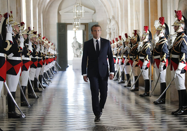 French President Emmanuel Macron walks through the Galerie des Bustes (Busts Gallery) to access the Versailles Palace's hemicycle to address both the upper and lower houses of the French parliament at a special session in Versailles, near Paris, Monday, July 9, 2018.