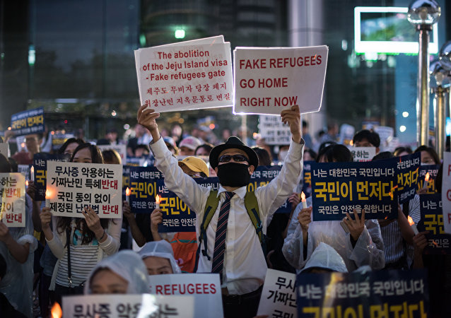 Anti-immigration activists attend a protest against a group of asylum-seekers from Yemen, in Seoul on June 30, 2018