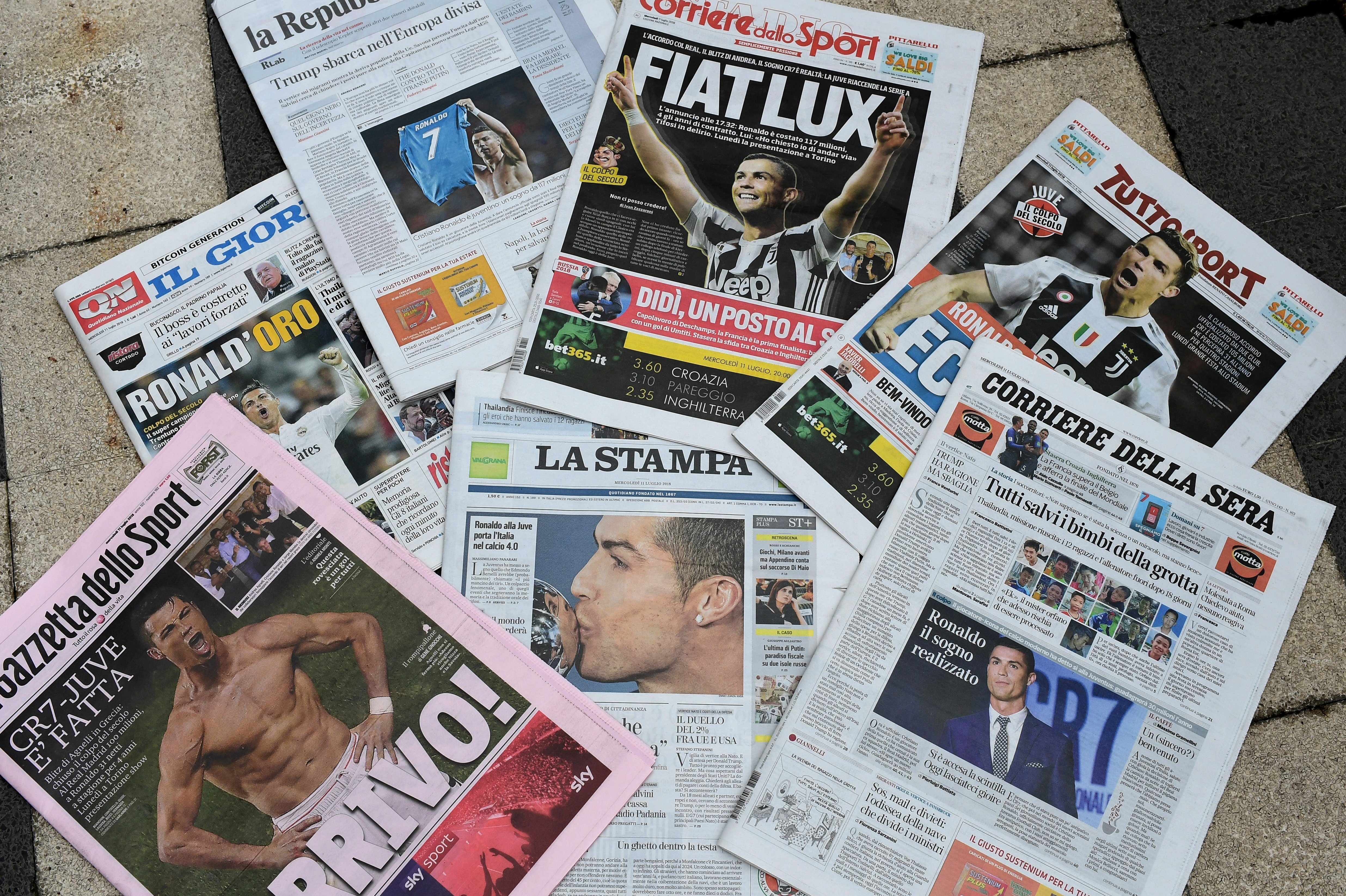 A picture taken on July 11, 2018 in Milan shows the Italian newspapers front pages enlightening the arrival of Portugal's Cristiano Ronaldo at the Italian Serie A football club Juventus Turin