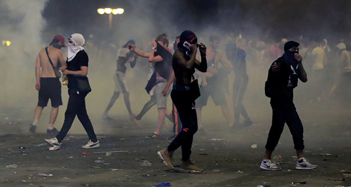 France fans are seen during clashes on the Champs-Elysees avenue after France win the Soccer World Cup final.
