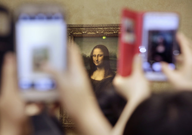 Tourists take pictures for Leonard de Vinci's La Joconde painting, Mona Lisa, at the Louvre museum in Paris, France, Thursday, Nov.19, 2015