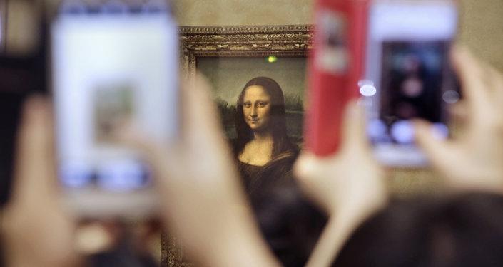 Tourists take pictures for Leonard de Vinci's La Joconde painting, Mona Lisa, at the Louvre museum in Paris, France, Thursday, Nov.19, 2015
