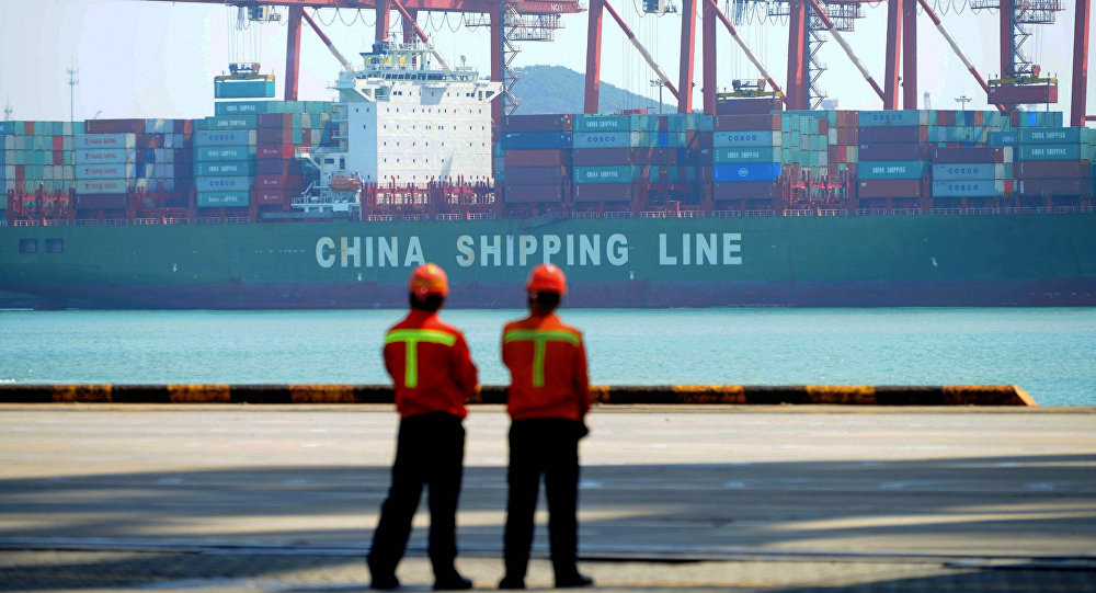 Chinese workers stand on a pier before a cargo ship at a port in Qingdao, east China's Shandong province on April 13, 2017
