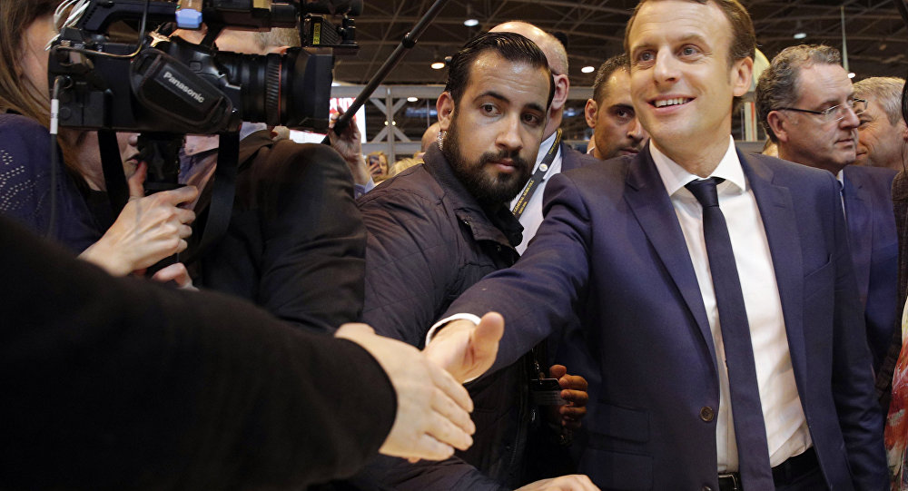 Emmanuel Macron, center, flanked by his bodyguard, Alexandre Benalla, left, visits the Agriculture Fair in Paris, Wednesday, March 1, 2017