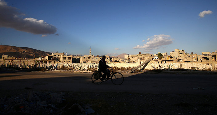 A man rides a bicycle near a cemetery in the rebel-held besieged town of Douma, eastern Ghouta in Damascus, Syria November 1, 2016.