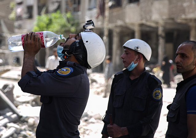 (File) Syrian civil defence volunteers, known as the White Helmets, take a break as they work at the site of a reported air strike in the rebel-held town of Douma, on the eastern outskirts of the capital Damascus, on October 5, 2016