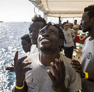Migrants aboard the Open Arms aid boat, of Proactiva Open Arms Spanish NGO, react as the ship approaches the port of Barcelona, Spain, Wednesday, July 4, 2018. The aid boat sailed to Spain with 60 migrants rescued on Saturday in waters near Libya, after it was rejected by both Italy and Malta