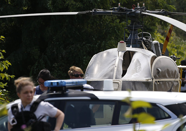 This picture taken on July 1, 2018 in Gonesse, north of Paris shows police near a French helicopter Alouette II abandoned by French armed robber Redoine Faid after his escape from prison in Reau