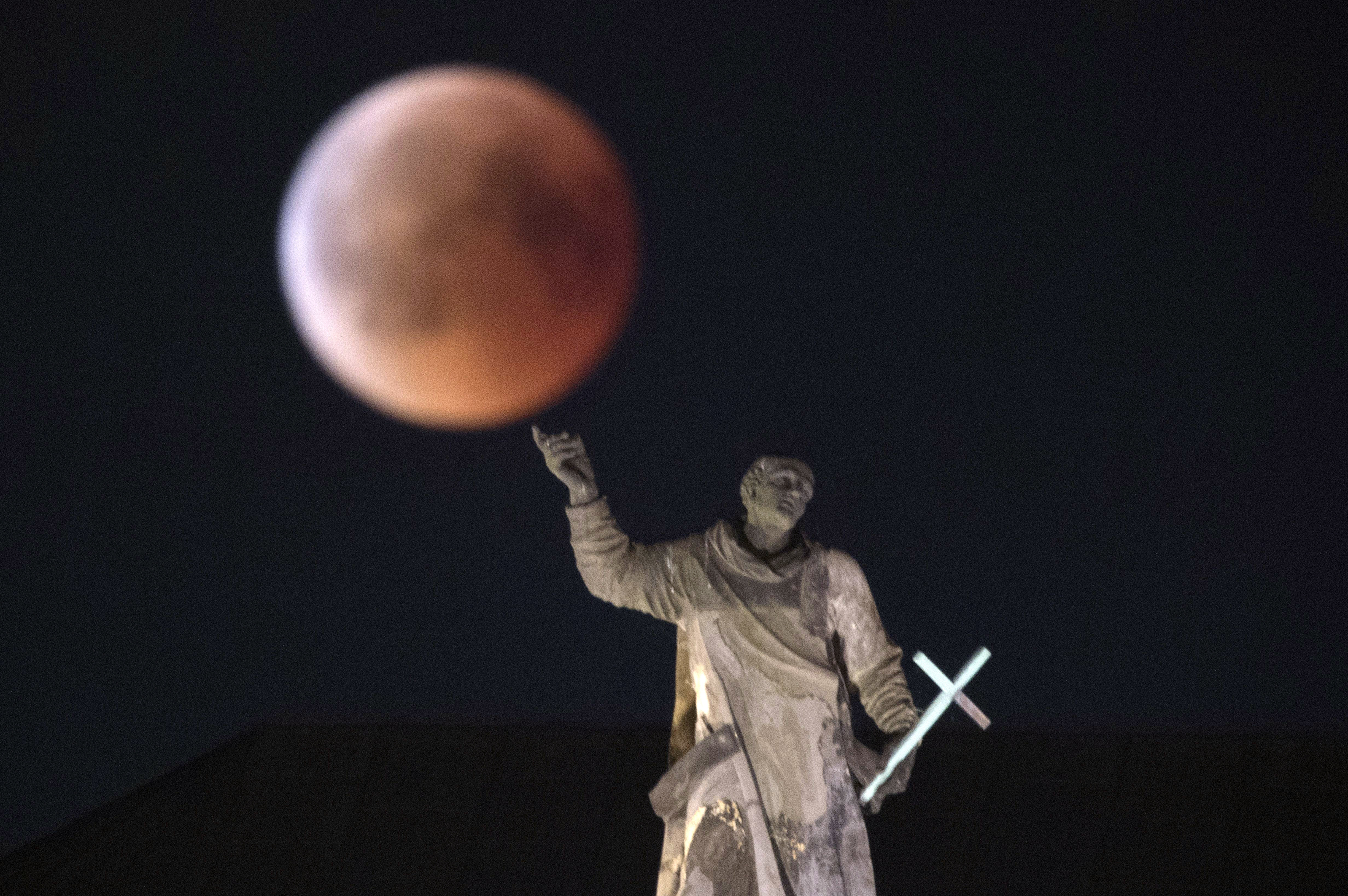 The moon turns red during a total lunar eclipse, as seen from Dresden, Germany, Friday, July 27, 2018. Skywatchers around much of the world are looking forward to a complete lunar eclipse that will be the longest this century.
