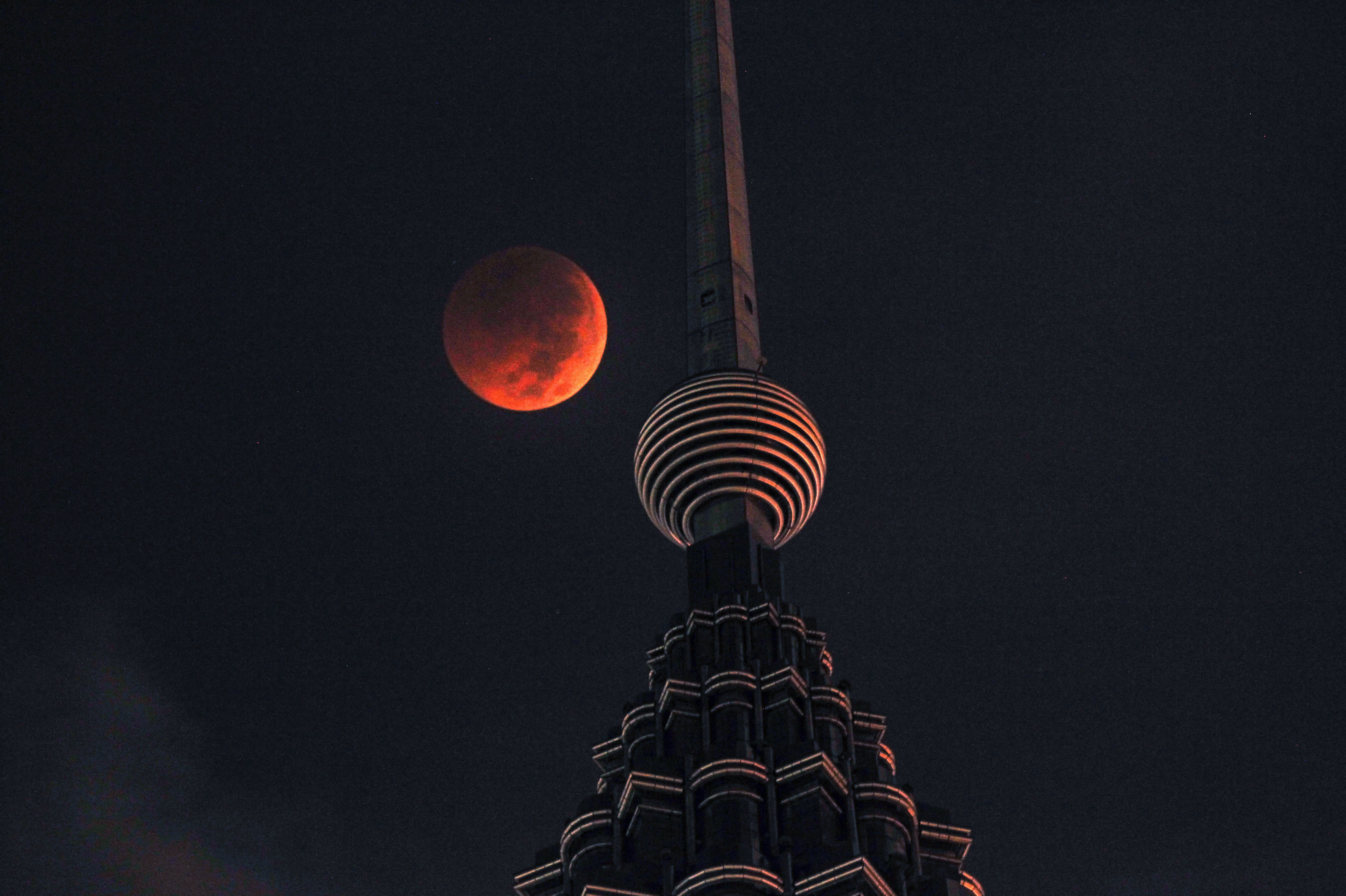 A full moon sets over Petronas Twin Tower during a complete lunar eclipse in Kuala Lumpur, Malaysia, Saturday, July 28, 2018. Skywatchers around much of the world are looking forward to a complete lunar eclipse that will be the longest this century.